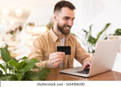 Young handsome bearded man doing online shopping in his laptop using bank card to pay online during break at cafe, lunch time