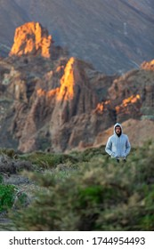 A young handsome bearded man is hiding behind a bush during a sunset in Teide Mountain, Tenerife