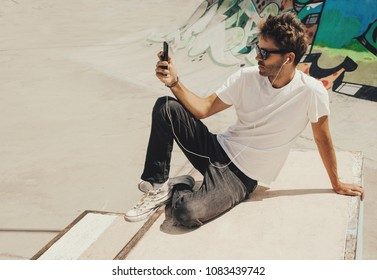 Young handsome bearded man os sitting next to graffiti wall background in skate park with a phone in his hand and wearing a white blank t-shirt and sunglasses. Horizontan mock up style.