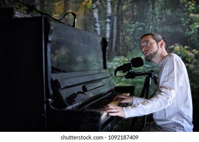 Young handsome bearded man playing piano and singing on forest background