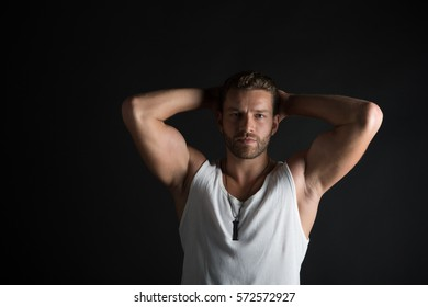 young handsome bearded man sexy macho with muscular hands and beard on serious face in white vest posing in studio on black background