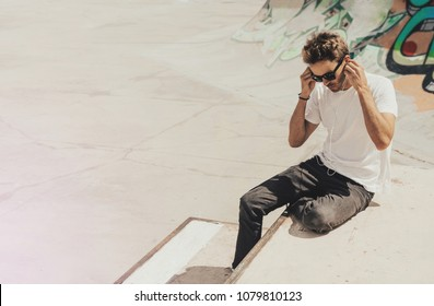 Young handsome bearded man sitting next to a graffiti wall background in skate park is wearing a white blank t-shirt and sunglasses. Horizontal mock up style.