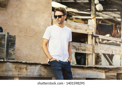 Young handsome bearded man is staying on a western city background surrounded by wooden fence. Guy is wearing a white empty t-shirt without logo. Horizontal mock-up style.