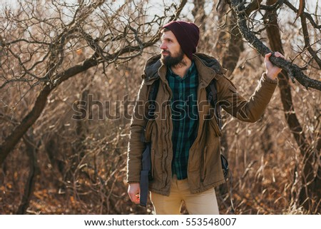64246e8e young handsome bearded man walking in forest with a touristic backpack,  autumn style, warm