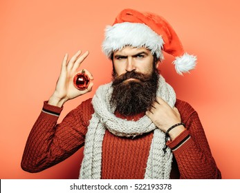 young handsome bearded santa claus man with long beard in red sweater and new year hat in scarf holds decorative christmas or xmas ball on orange studio wall background