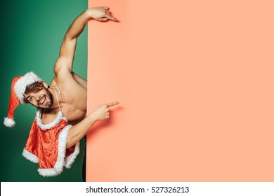 young handsome bearded sexy macho christmas smiling man with long beard in red santa claus hat and coat with muscular bare torso in xmas holiday or new year on colorful background, copy space