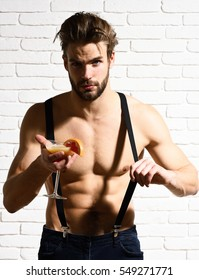 young handsome bearded sexy macho man with stylish beard shows six packs and abs on muscle torso on athletic body in pants with suspenders holding glass of alcoholic cocktail on brick wall background