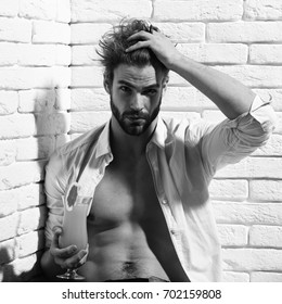 young handsome bearded sexy macho man with stylish beard in unbuttoned white shirt and muscular bare torso on athletic body holding glass of alcoholic orange cocktail on white brick wall background