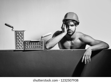 young handsome bearded tired macho man builder with sexy muscular athletic strong body has strong hands in orange hard hat or helmet with brick and tool, copy space