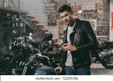 young handsome biker in black leather jacket with classic motorbike in workshop