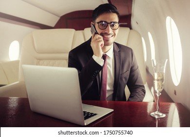 Young handsome billionaire in his private jet drinking champagne, talking on phone with buisness partners, sitting at table with laptop open