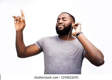 Young handsome black man, listening to music on headphones, smiling face expression, positive mood, happy emotion, isolated on white background, african american youth, hipster style, student