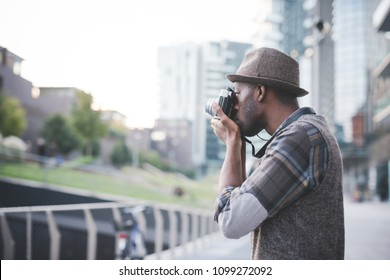 young handsome black millennial man outdoor using camera taking photos - influencer, photographer, blogger concept