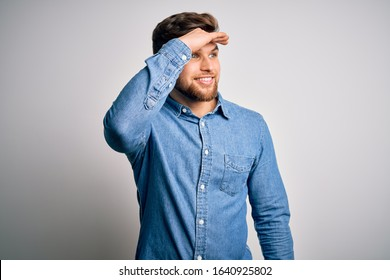 Young handsome blond man with beard and blue eyes wearing casual denim shirt very happy and smiling looking far away with hand over head. Searching concept.
