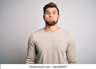 Young handsome blond man with beard and blue eyes wearing casual sweater puffing cheeks with funny face. Mouth inflated with air, crazy expression.