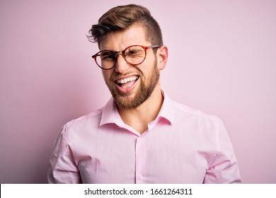 Young handsome blond man with beard and blue eyes wearing pink shirt and glasses winking looking at the camera with sexy expression, cheerful and happy face.
