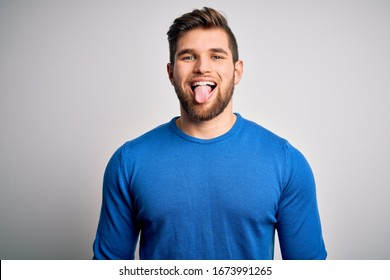 Young handsome blond man with beard and blue eyes wearing casual sweater sticking tongue out happy with funny expression. Emotion concept.