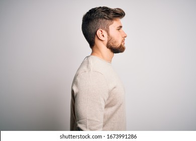 Young handsome blond man with beard and blue eyes wearing casual sweater looking to side, relax profile pose with natural face with confident smile.