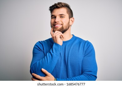 Young handsome blond man with beard and blue eyes wearing casual sweater looking confident at the camera with smile with crossed arms and hand raised on chin. Thinking positive.