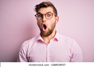 Young handsome blond man with beard and blue eyes wearing pink shirt and glasses afraid and shocked with surprise expression, fear and excited face.