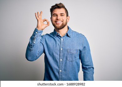 Young handsome blond man with beard and blue eyes wearing casual denim shirt smiling positive doing ok sign with hand and fingers. Successful expression.