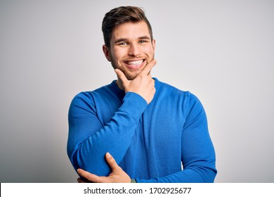 Young handsome blond man with beard and blue eyes wearing casual sweater looking confident at the camera smiling with crossed arms and hand raised on chin. Thinking positive.