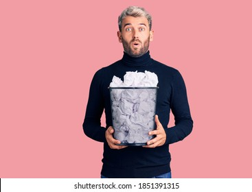 Young handsome blond man holding paper bin with crumpled papers scared and amazed with open mouth for surprise, disbelief face