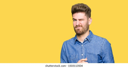 Young handsome blond man wearing casual denim shirt disgusted expression, displeased and fearful doing disgust face because aversion reaction. With hands raised. Annoying concept.
