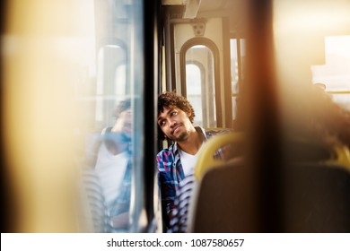 A young handsome bored man is sitting in a bus seat leaned and looking through the window as he waits for arrival to his destination.