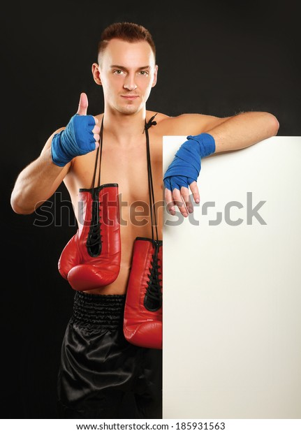 Young handsome boxer man standing near board and showing ok, isolated on black background