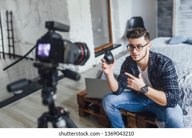 A young, handsome boy blogger in glasses takes a video of a new mouse for a computer, in a bed in a loft room.