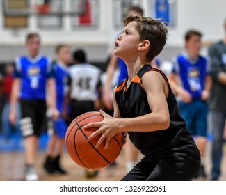 Young handsome boy playing in a basketball game