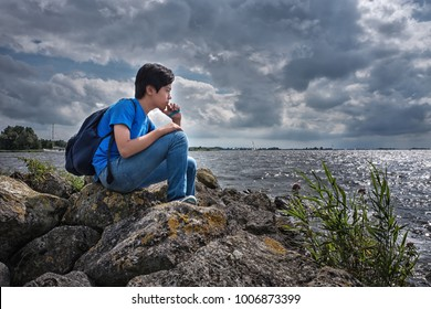 Young handsome boy pondering and looking over the sea