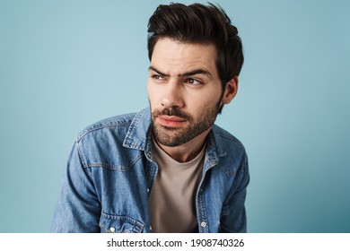 Young handsome brooding guy thinking and looking aside isolated over blue background