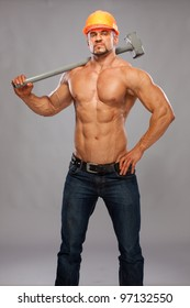 Young and handsome builder with a sledgehammer and sexy body