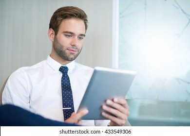 Young handsome business executive sitting in a bright space and looking at the screen of the digital tablet he is holding