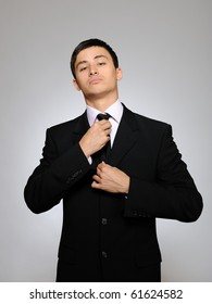 Young handsome business man in black suit and tie. gray background