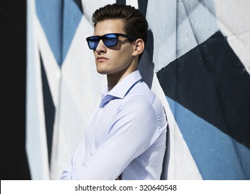Young handsome business  man in blue  suit and glasses watching against painted wall