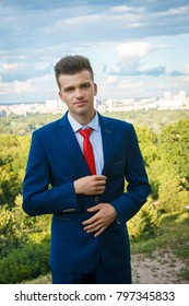 Young handsome business man in blue suit with white shirt and red tie standing on a hill on a background of city, greenery and sky with clouds