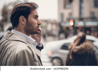 Young handsome business man chatting on his phone, waiting on the traffic light to cross the street, busy life