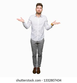 Young handsome business man clueless and confused expression with arms and hands raised. Doubt concept.