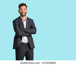 Young handsome business man crossing arms, smiling and relaxed