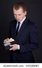 young handsome business man holding leather purse with euro banknotes
