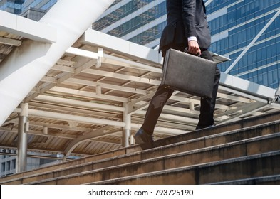 young handsome business man holding briefcase and walking up the stairs going to work time at morning in the city, determination, confidence, lifestyle, rush hour, grow up and successful concept