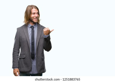 Young handsome business man with long hair over isolated background smiling with happy face looking and pointing to the side with thumb up.