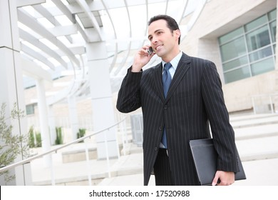 A young, handsome business man at the office building on phone