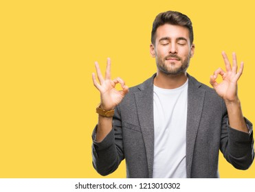 Young handsome business man over isolated background relax and smiling with eyes closed doing meditation gesture with fingers. Yoga concept.