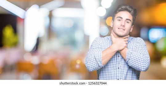 Young handsome business man over isolated background shouting and suffocate because painful strangle. Health problem. Asphyxiate and suicide concept.