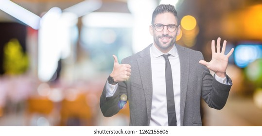 Young handsome business man over isolated background showing and pointing up with fingers number six while smiling confident and happy.
