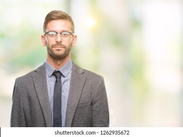Young handsome business man over isolated background with serious expression on face. Simple and natural looking at the camera.